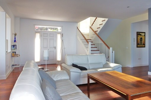 The large living room with entrance area, elegant staircase and access to the kitchen
