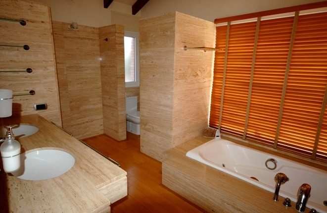 Inviting bathroom with double sinks, tub and separate toilet