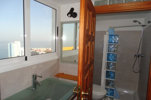 Bathroom has large windows and clear sea view